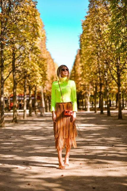 Thássia Naves veste blusa neon verde, saia de franjas e sandália nudist.