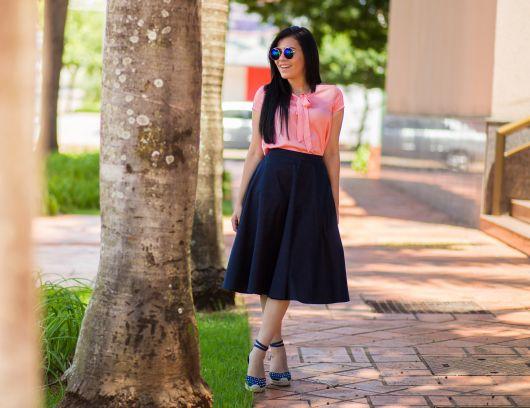 Modelo veste saia midi azul-marinho,blusa rosa e espadrille jeans.