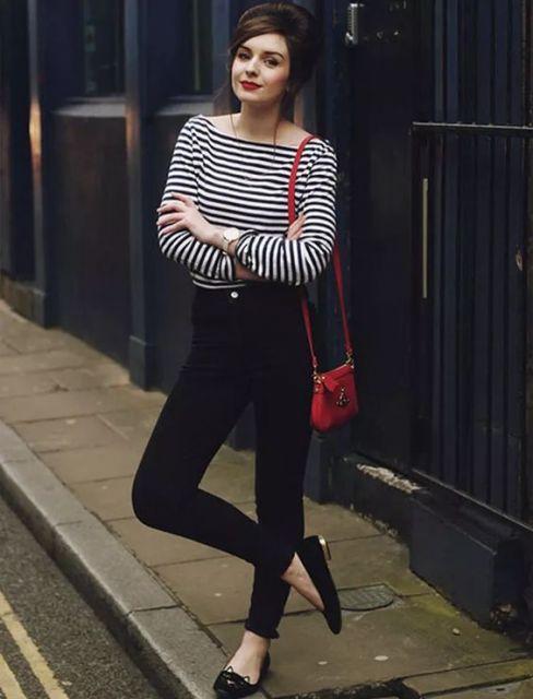 Look com blusinha listrada em preto e branco, calça jeans e sapatilha preta com bolsa de ombro vermelha.