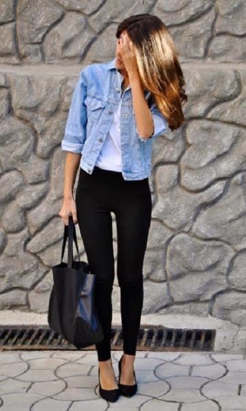 Modelo veste jaqueta jeans azul claro, calça preta e sapatilha e bolsa no mesmo tom