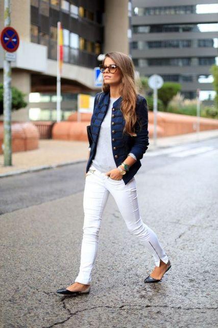Modelo veste calça jeans branca, sapatilha preta, jaqueta jeans escura, blusa cinza e óculos.