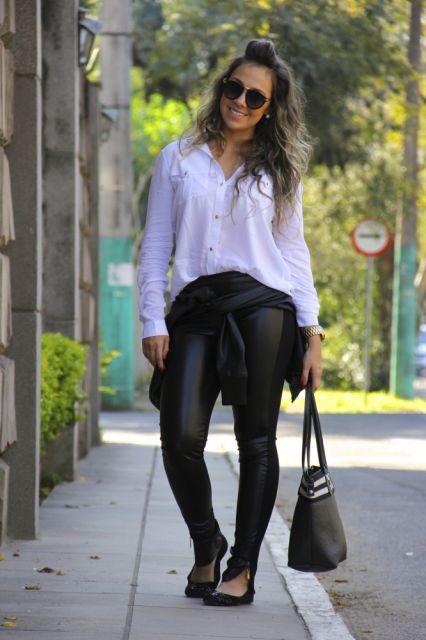 Modelo veste calça em couro, blusa branca larguinha, bolsa e sapatilha preta.