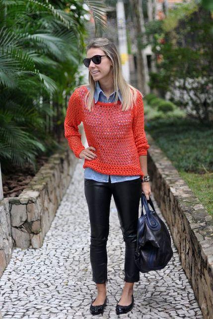 Modelo veste calça em imitação de couro, camisa azul, com sobreposição de crochê laranja, bolsa e sapatilha preta.