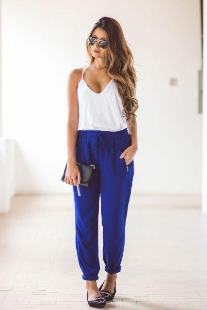 Modelos veste calça larguinha em tons de azul royal e blusa de alcinha branca.