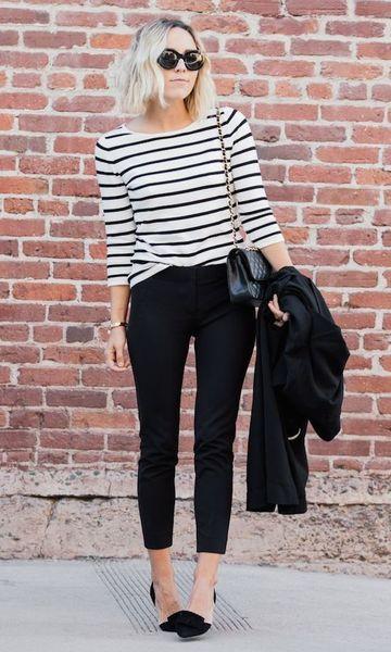 Modelo veste calça em alfaiataria na cor preta , sapatilha, blusa listrada em preto e branco e bolsa pequena de ombro.