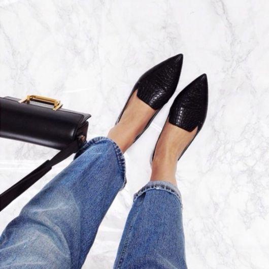 Pés calçam sapatilha preta de bico modelo simples.