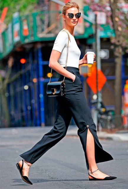 Modelo veste calça em alfaiataria com fenda na cor verde escuro, blusa branca, bolsa de ombro e sapatilha preta com amarrações.