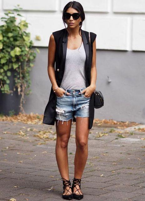 Modelo veste look com bermuda jeans, blusa cinza básica, maxi colete, sapatilha e bolsa preta.