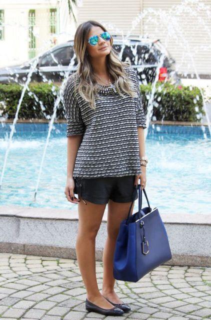 Thássia naves veste blusa larguinha com short preto em couro, sapatilha preta e bolsa azul royal.