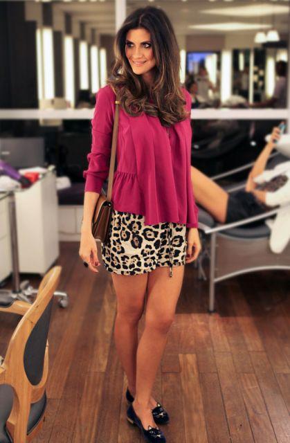 Isabela Fiorentino veste saia reta estampada de oncinha, blusa rosa larguinha e sapatilha preta.
