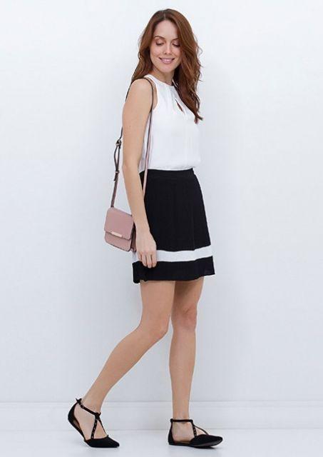 Modelo veste saia preta com detalhe em branco, blusa regata no tom de branco, sapatilha preta e bolsa de ombro rosê.