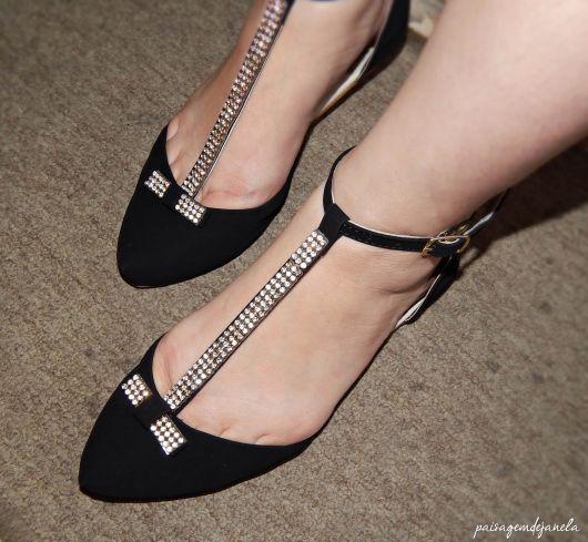 Pés calçam modelo de sapatilha preta com detalhes em strass.