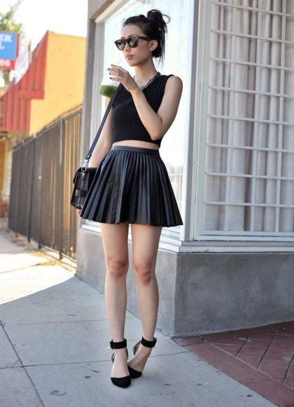 Modelo veste blusa top cropped preta, saia curta plissada com bolsa de ombro e sapatilha no mesmo tom.