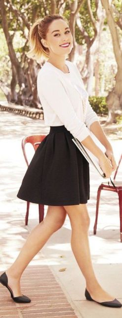Look com saia plissada curta, blusa branca meia manga e sapatilha preta.
