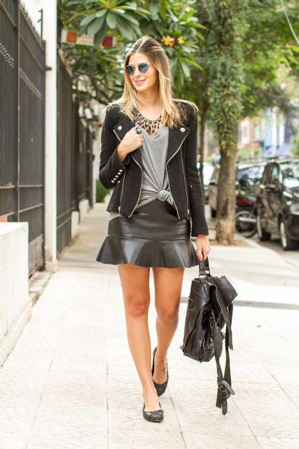 Modelo veste saia reta com detalhe plissado, blusa cinza com jaqueta elaborada, bolsa de couro preta e sapatilha na mesma cor.