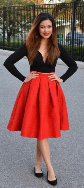 Modelo veste saia midi laranja, blusa cropped preta e sapatilha no mesmo tom.