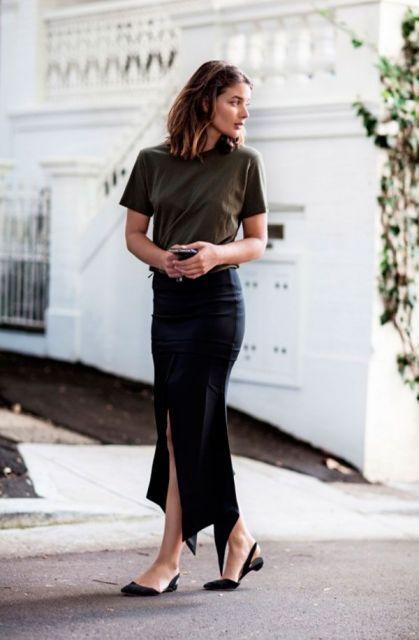 Modelo veste saia midi justa com fenda, camiseta simples verde musgo e sapatilha preta.