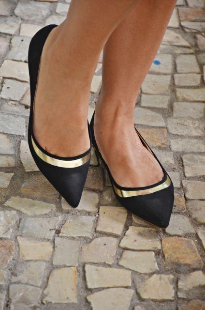 Pés calçam modelo de sapatilha preta bico fino, com detalhes de fita dourada.