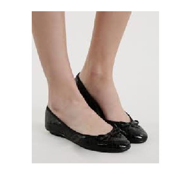 Pés calçam modelo de sapatilha preta com bico arredondado.