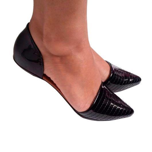 Pés calçam modelo de sapatilha preta lisa bico fino em verniz.