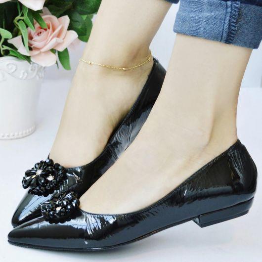 pés calçam modelo de sapatilha preta bico fino em verniz, com detalhe de flor.