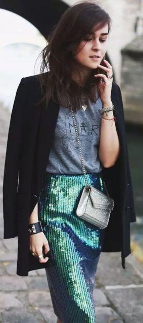 Modelo veste saia de paêtes e blusa cinza com blazer preto e bolsa cinza.