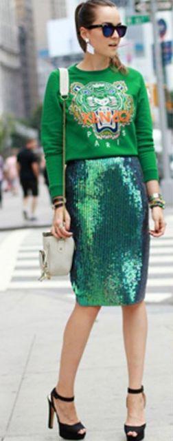 Modelo veste, blusa verde manga longa, saia metalizada, bolsa de ombro cinza e sandália preta.