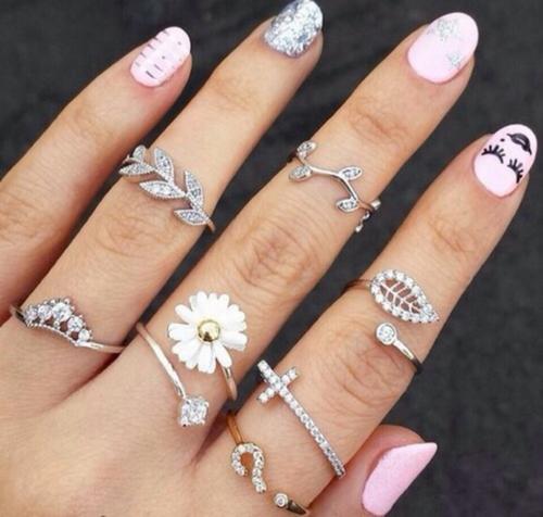 Mão com anéis brilhantes de três dedos.