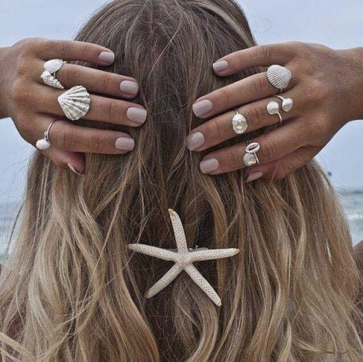 Modelo com as mãos atrás da cabeça mostra anéis inpirados nas sereias e acessório de estrela-do-mar nos cabelos.