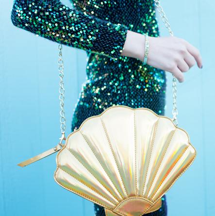 Modelo com bolsa concha na cor dourada.