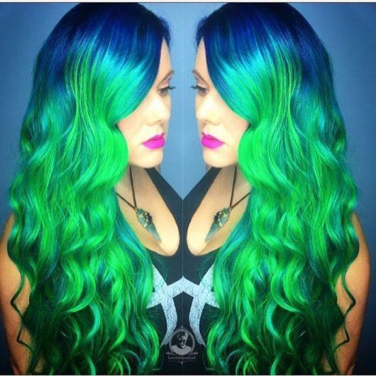 Cabelo ondulado colorido em tons de verde com azul.