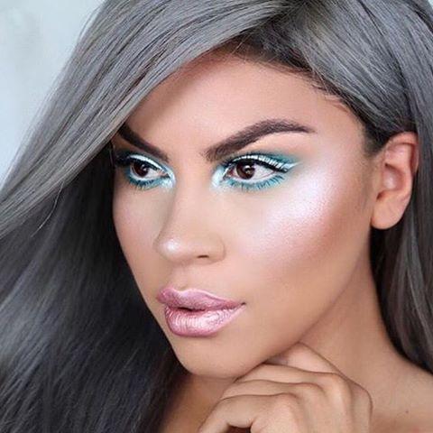 Maquiagem com olhos destacados na cor azul cintilante, pele iluminada e batom rosa também cintilante.