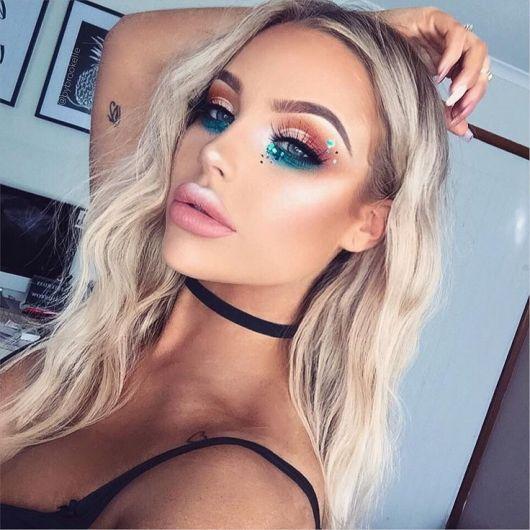 Maquiagem em tons de azul e marrom nos olhos, pele iluminada e batom rosa matte.