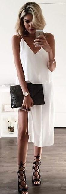 Look com slip dress branco com fenda, sandália de amarrações preta e bolsa na mesma cor.