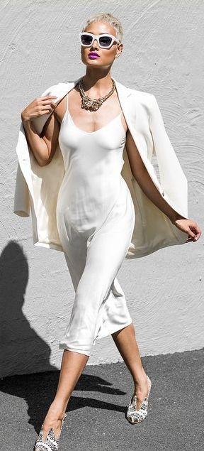 Modelo veste vestido branco, com blazer no mesmo tom e sapatilha de bico estampada.