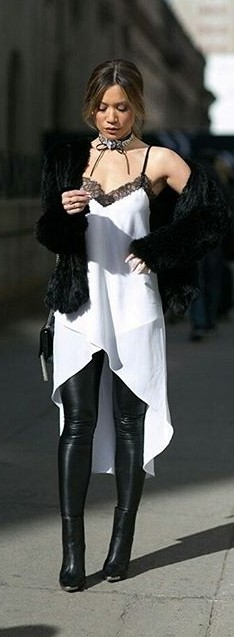 Modelo veste, vestido branco de alcinhas, casaco de pele preto e bota com calça de couro.