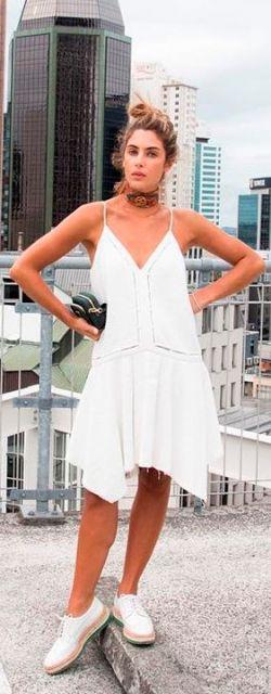 Modelo veste vestido branco de alcinhas, tênis na mesma cor e bolsa de mão preta.