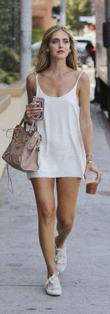 Look com vestido slip dress curto, bolsa de ombro rosê e tênis branco.