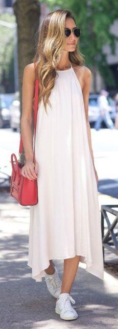 Look com vestido branco casual comprido, bolsa de ombro vermelha e tênis branco.