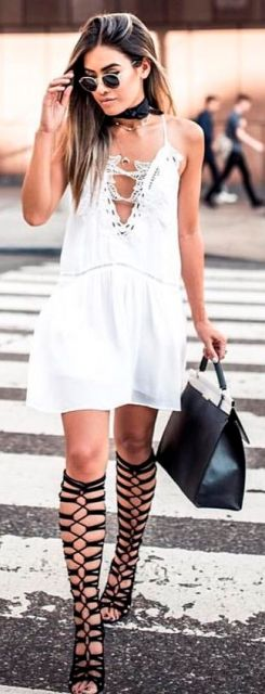 Modelo veste, slip dress branco com decote, sandália gladiadora preta e bolsa no mesmo tom.