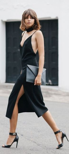 Modelo veste vestido preto com fenda, sandália preta e bolsa na mesma cor.