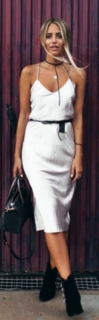 look com vestido branco, cinto preto, botinha e bolsa no mesmo tom.
