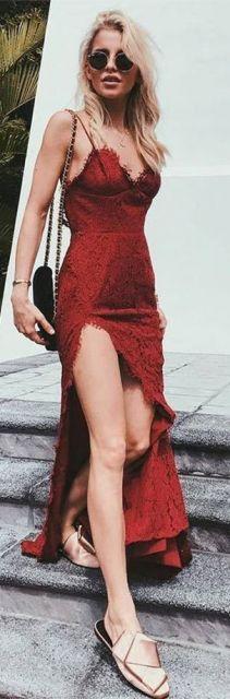 Modelo veste vestido vermelho de alcinha, longo com fenda, bolsa preta de ombro e sapatilha nude.