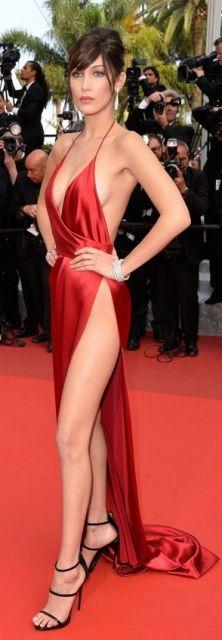 Modelo veste slip dress em cetim vermelho com fenda até a cintura e decote profundo com sandália preta de duas tiras.