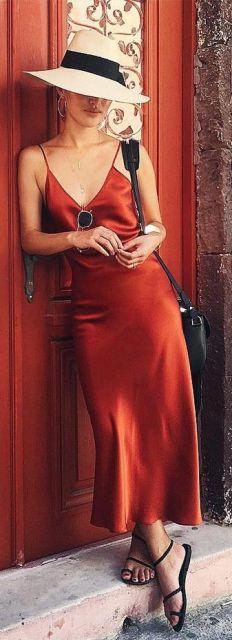 Look com vestido em cetim vermelho, com bolsa preta de ombroe rasteirinha no mesmo tom.