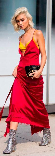 Look com vestido vermelho longo, top em tom amarelo, bolsa preta de mão e sapato glitter.