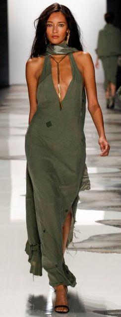Modelo veste vestido verde longo com fenda, e echarpe no mesmo tom, com sandália preta.