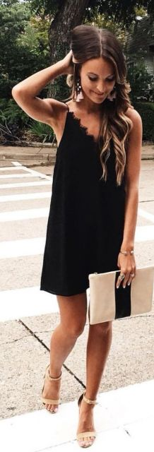 Look com vestido preto curto, bolsa nude com preto e sandália bege.
