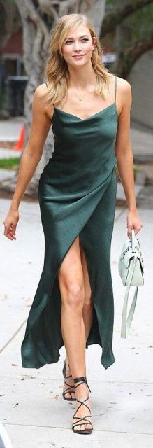 Look com vestido verde longo de alcinhas com fenda, bolsa de mão branca e rasteirinha com amarrações.