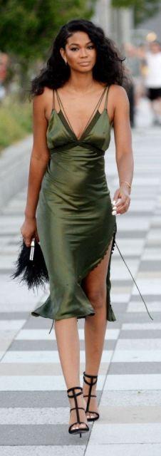 Look com vestido verde tamanho médio com fenda, bolsa pompom preta e sandália na mesma cor.